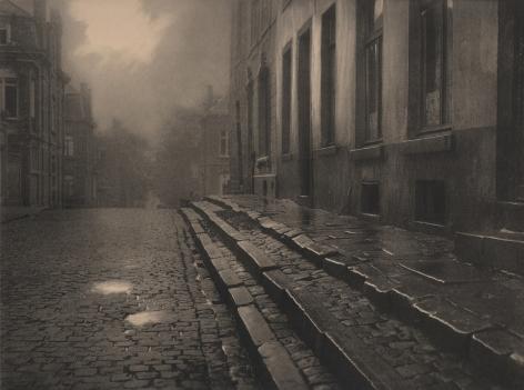 09. Léonard Misonne, [title illegible], c. 1930. Wet, cobbled, residential street and steps in soft light. Sepia-toned print.