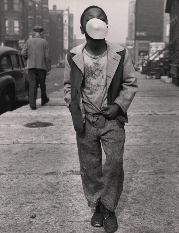Marvin E. Newman, Chicago, ​1950. A boy walks on the sidewalk toward the camera, hands in pockets, with a chewing gum bubble obscuring most of his face.