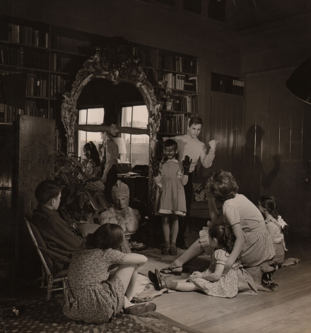 Louise Dahl-Wolfe, Charades Before Bedtime, Editorial in Diana Vreeland's House, 1942. A group of children sits on the floor looking toward two standing children. One has hands raised in black gloves and facepaint, the other stands behind her pointing a thumb to the right of the frame.