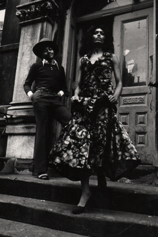 10. Anthony Barboza, Harlem, NY, ​1970s. Sharply-dressed couple in a dress and suit standing at a building entrance.