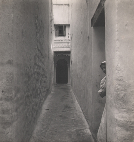 Cecil Beaton, Tangier, ​c. 1945. A child peeks out from a doorway on the right side of an alleyway.