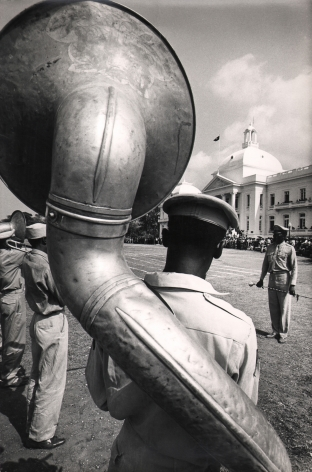 02. Graham Finlayson, Haiti - Presidential band before the Palace, c. 1958–1966. Rear view of a uniformed man with a large wind instrument strapped to his back.