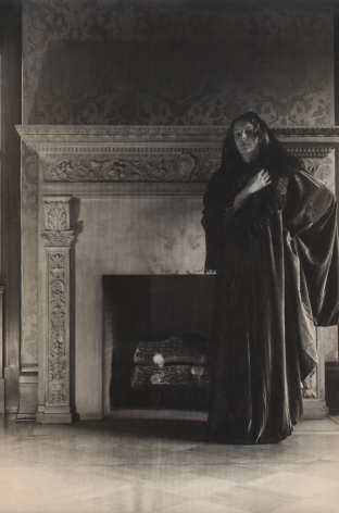 PaJaMa, Margaret French, Hoboken, ​c. 1945. A woman stands wearing draping fabric in front of a fireplace. One hand is on her hip and the other held to her chest.