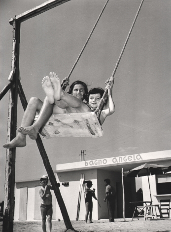 Nino Migliori, Children by the Sea, 1954. Two girls on a swing photographed from a low angle.