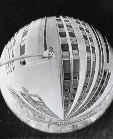 06. New York Journal, A Nice Round Figure, 1962. Fish-eye lens view of three figures on a balcony of the Empire State Building. The image is distorted so that the view is a circle.