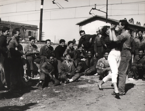Federico Garolla, Valeria Moriconi - Railway between Rome & Florence, 1959. A large group of men watch on, smiling, as a couple dances in front of them.