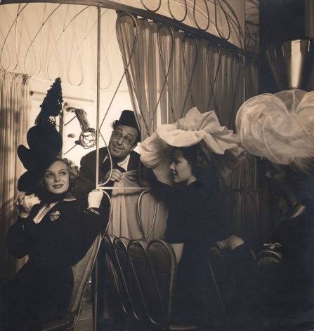 Louise Dahl-Wolfe, Ed Wynn & Jane Pickens In Boys & Girls Together, 1940. A man in glasses and a top hat peers out from behind a curtain. Three women in large billowing hats are seated in the foreground.