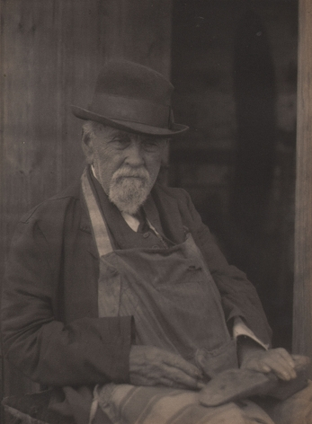 Doris Ulmann, Untitled (Cobbler), ​1928–1934. Seated man in a hat and apron with hands in his lap holding a shoe.