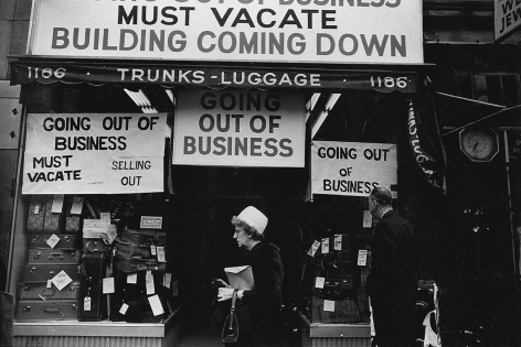 "7. Simpson Kalisher, Untitled, ​1962. Two pedestrians pass a storefront with various ""Going out of business"" signs and stacks of suitcases in the shop window."