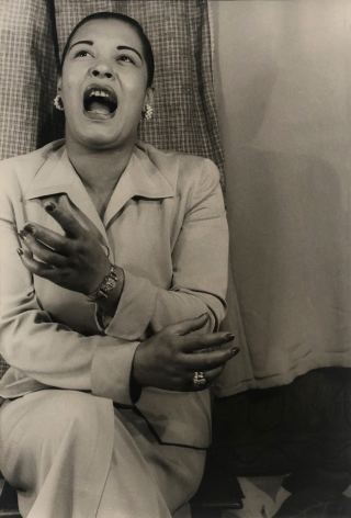 03. Carl Van Vechten, Billie Holiday, 1949. Seated portrait of the singer, eyes cast up, one hand raised, and mouth open in song.