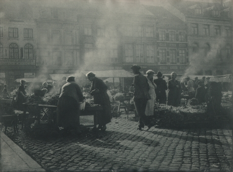 06. Léonard Misonne, Untitled, c. 1937. Many figures on a cobbled market street with steam rising from various booths. Gray/green-toned print.