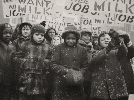 """Gordon Coster, Untitled, c. 1938. Crowd of children in winter coats holding signs above their heads. Signs are in partial view, but the words """"MILK"""" AND """"JOB"""" can be seen."""