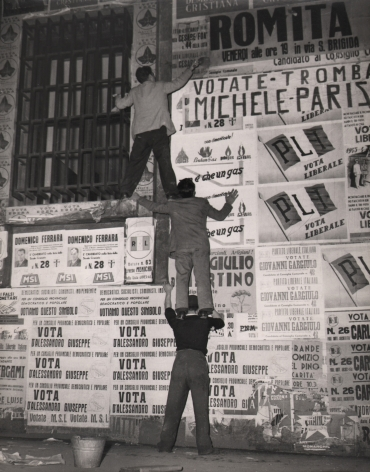 Federico Garolla, Elezione a Napoli, ​1948. Three men stand on each others shoulders to reach a high point on a wall covered in election posters.