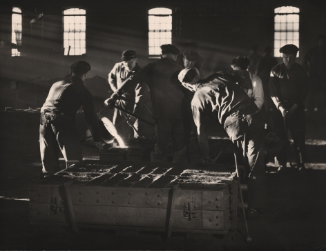 Ralph Bartholomew, Steinway Piano Factory, c. 1935. Dark factory scene with light streaming in from the left. Workers perform various tasks including pouring molten metal.