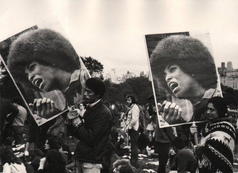 02. Beuford Smith, Angela Davis demonstration, Central Park, NY, ​1972. A crowd of protesters; two hold large signs with photos of Angela Davis.