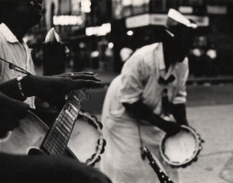 04. Beuford Smith, Sunday in Harlem, 1968. Figures playing tambourines and a guitar on the street. Focus is on the lower left of the frame on the neck of a guitar and the player's left hand.