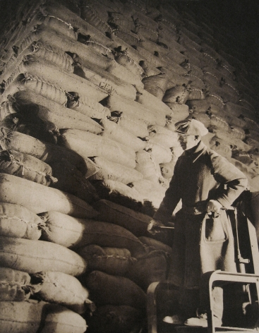 Harold Haliday Costain, Edgewater, NJ Sugar Refinery, 1935. A man stands in the lower right of the frame in front of stacked sugar sacks.