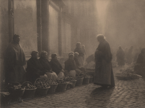 07. Léonard Misonne, Choix difficile, 1933. Older woman stands on a cobbled street facing a row of women seated with baskets of produce. Sepia-toned print.