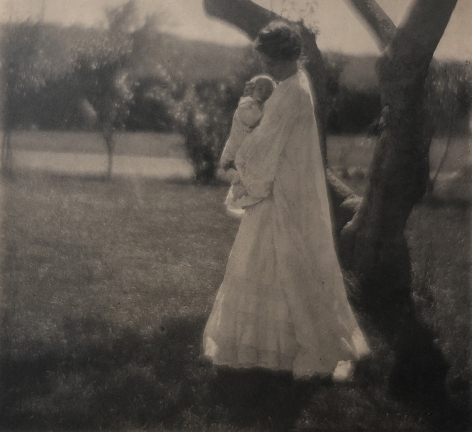 04. Gertrude Käsebier, Blossom Day, 1904. A woman in a long white dress stands beneath a tree holding a baby to her chest.