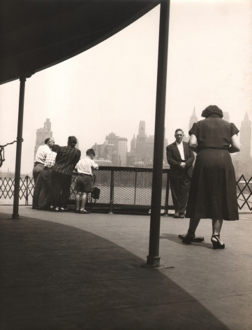 06. Simpson Kalisher, Untitled (Staten Island Ferry), ​c. 1949. Figures standing on a covered pier with a city skyline in the background.