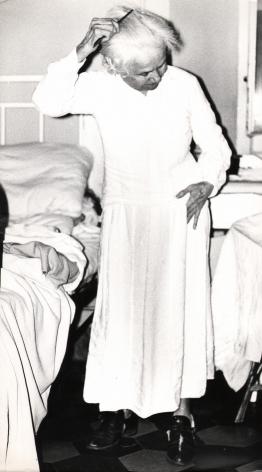 01. Mario Giacomelli, Verrà la morte e avrà i tuoi occhi, 1966–1968. High contrast image. An old woman stands by a bed, combing her hair.
