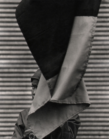 07. Beuford Smith, Woman & Flag, Harlem, 1969. A small portion of a woman's face is seen from behind a large flag that hands above and in front of her.