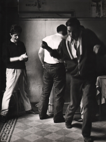 Mario Cattaneo, Jukebox, c. 1960. One man dances, blurred with motion, while another looks on clapping and a third man faces away from the camera towards the jukebox.