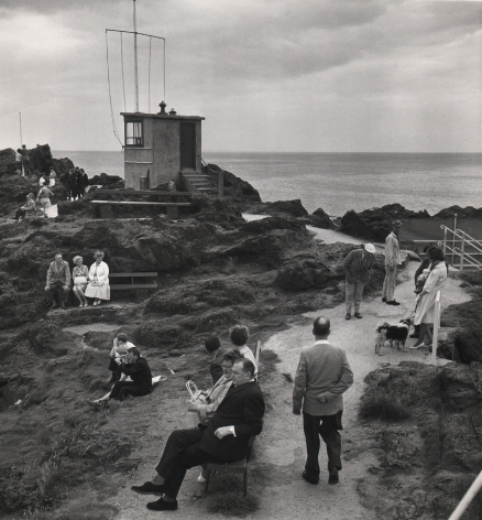 14. C. O'Gorman, A holiday scene at North Berwick with everybody doing something as though compelled by the traditions of seaside behaviourism, 1963. Seaside pathway with scattered figures sitting and standing. A flagpole and small structure stand in the midground left.