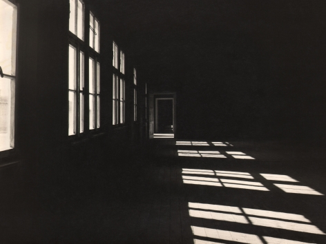 Luciano d'Alessandro, Mauthausen: Il Dormitorio, ​c. 1960. A dark hall with windows along the left casting light onto the floor on the right.