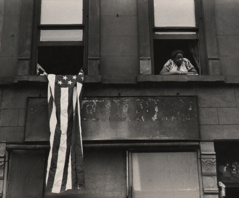 09. Beuford Smith, Flag Day, Harlem, 1976. Detail of two windows of an apartment building; a woman leans out of the right window, an American flag hangs from the left.
