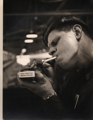 """Gordon Coster, Untitled, c. 1942. A young man lights a cigarette holding a matchbox that reads """"Keep Our Gun Mounts Rolling"""""""
