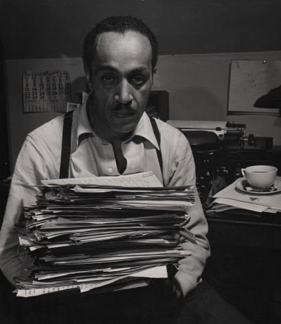 Wayne F. Miller, Willard Motley, 1947. Subject looks into camera while holding a tall stack of papers.