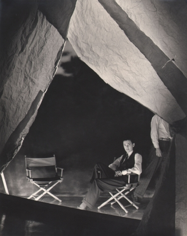 George Platt Lynes, Alfonso Ossorio, n.d. Subject is seated on the right of two directors' chairs beneath backlit fabric hanging from above.