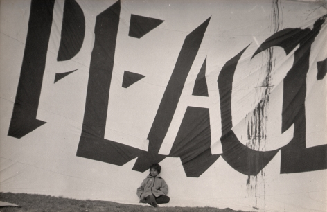 "8. LeRoy Henderson, Central Park Anti-Vietnam War Rally, 1968. Young child sits against large banner that reads ""PEACE"" and fills the frame."