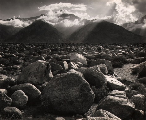 Ansel Adams, Mt. Williamson from Manzanar, Owens Valley, Calif., ​1944. Landscape. Rocks fill the lower half of the frame. Background of mountains and light beams traveling diagonally down and left through clouds.