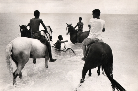 04. Mike Andrews, Nassau, Bahamas. Stable boys exercising racehorses on Cable Beach, c. 1960. Four boys on horses in knee-deep water. A fifth boy is in the water with a bicycle.