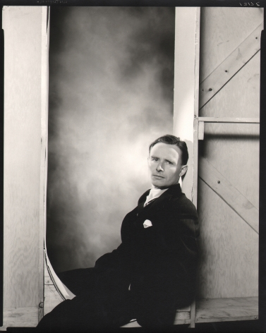George Platt Lynes, Christopher Isherwood, ​n.d. Subject is seated leaning to the right against a wooden studio wall.