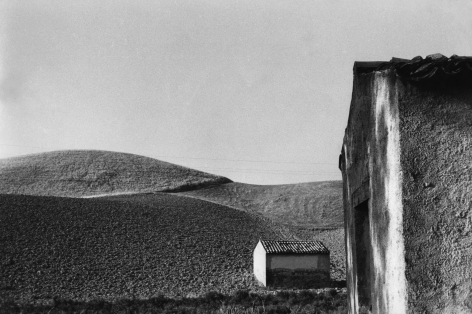 10. Frank Monaco, The buildings were once cottages of people who have emigrated, c. 1966. Hilly landscape and two one-room structures in the right foreground.