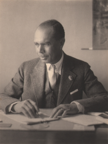 Doris Ulmann, James Weldon Johnson, c. 1925. Subject is seated at a desk, writing and looking to the left.