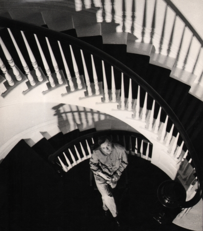 07. David Attie, Truman Capote (Holiday Magazine), 1958. Subject is seated on the landing of a winding staircase, looking up at the camera with legs crossed and hands in his lap.
