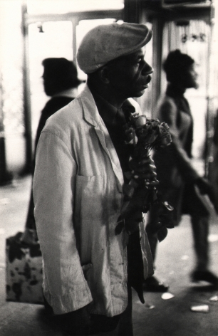 06. Beuford Smith, Man with Roses, 125th Street, 1972. Upper body portrait of a man facing the left of the frame holding a small bouquet of roses.