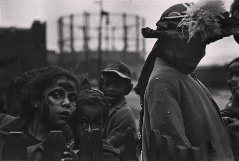 Marvin E. Newman, Chicago, ​1950. Children wearing face paint and a woman in a large feathered hat look to the camera in curiosity.