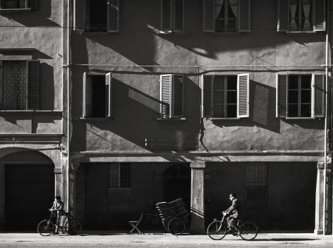 Nino Migliori, The house opposite, 1954. Two men ride bicycles in front of an apartment building
