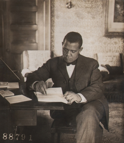 Underwood & Underwood, Booker T. Washington, 1906. Subject is seated at a desk, writing and looking down.