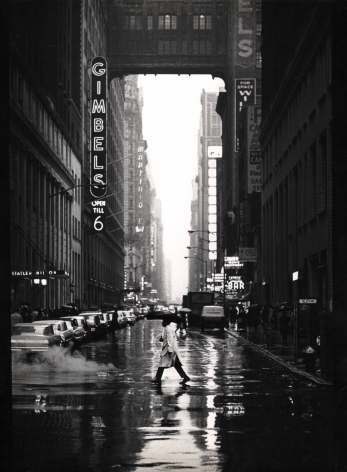 10. Jan Lukas, New York, 32nd Street, ​1964. A man with a trenchcoat and umbrella walks across a wet car-lined street. The neon sign for Gimbels is on the left midground.
