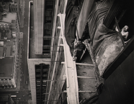 04. Anonymous, Beginning Repairs on Empire State, 1945. Above view of mid-repair building facade with rebar, tarp, and wood planks visible. A construction worker can be seen on the far right.