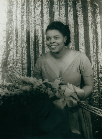 09. Carl Van Vechten, Carol Brice, 1947. Subject stands, smiling towards the left of the frame, holding a large bouquet.