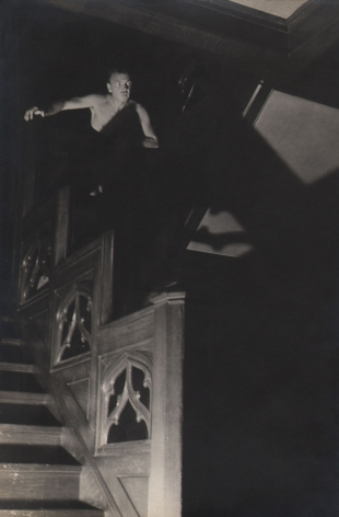 PaJaMa, Jared French, ​c. 1945. A man's upper torso emerges from shadows at the top of a staircase in the top left of the frame.