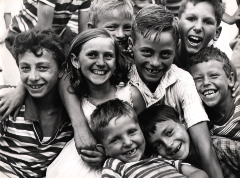 Mario Cattaneo, Untitled, c. 1960. A group of seven children huddled close together, smiling to the camera.