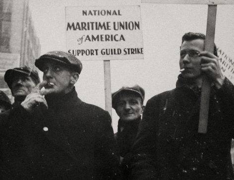 """Gordon Coster, W.P.A. Parade, Chicago, 1939. Four men walk in black coats on a snowy day, smoking cigarettes. One holds a sign that reads """"National Maritime Union of America Support Guild Strike"""""""